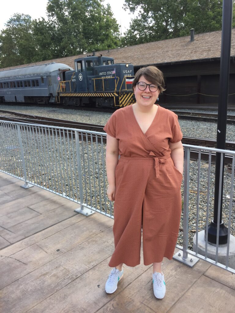 Jenna smiling in front of a train in a seersucker Zadie jumpsuit.